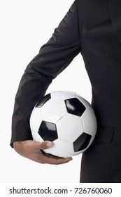 Man in business attire holding ball.