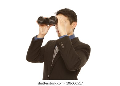 A man in business attire using binoculars (on white)