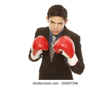 Man in business attire wearing boxing gloves in a fighting stance (on white)