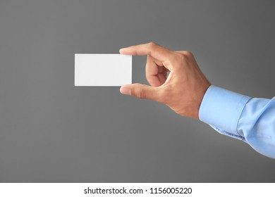 Man with business card on grey background
