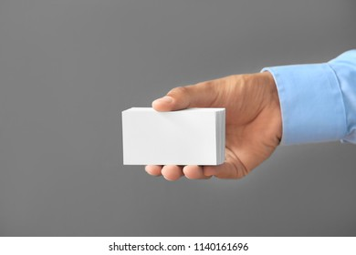 Man with business cards on grey background