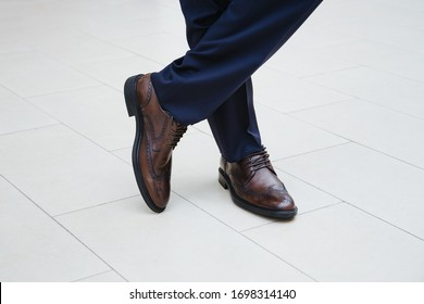 A man in business stylish shoes stands cross-legged and one heel lifted.