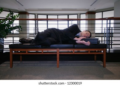 Man in a business suit asleep on a couch in an office hallway