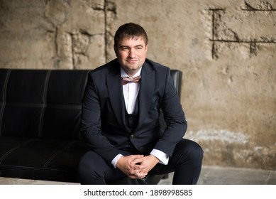 Man in business suit and bow tie on the sofa