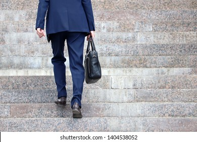 Man in a business suit with briefcase climbing steep stairs, male legs in motion on the steps. Concept of career, success, moving to the top, official or businessman