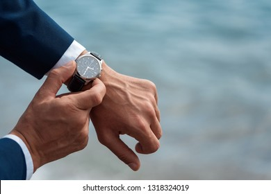 A man in a business suit checking a wrist watch on his hand on background  sea