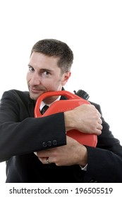 A man in a business suit clutching a red plastic gasoline can.