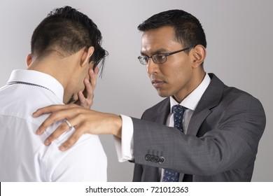Man in business suit consoles grieving friend