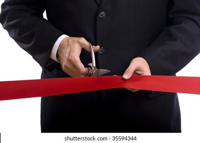 A man in a business suit cutting a red silk ribbon with shiny scissors, grand opening or beginning concept