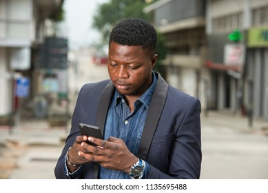 Man in business suit is enjoying modern mobile technologies in city.Concept of modern technologies order by phone.