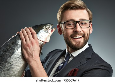 A man in a business suit with fresh salmon in his hand. Studio portrait.