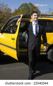 A man in a business suit gets out of a car