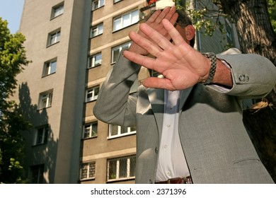 man in a business suit hiding his face from the photographer