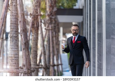 man in business suit holding cup of coffee. business lifestyle in coffee time at morning daylight.man feeling fresh and happy with confident of success.