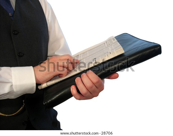 A man in a business suit holding a newspaper and a black briefcase.
