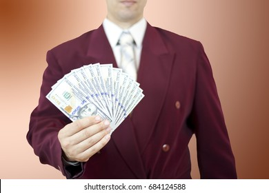 Man in a business suit holds a fan of hundred-dollar bills