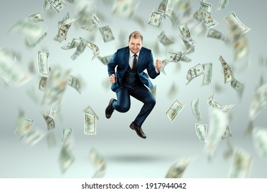 A man in a business suit jumps for joy against the background of falling dollars, rain of money. Business concept, bookmaker, sports betting, investment, passive income
