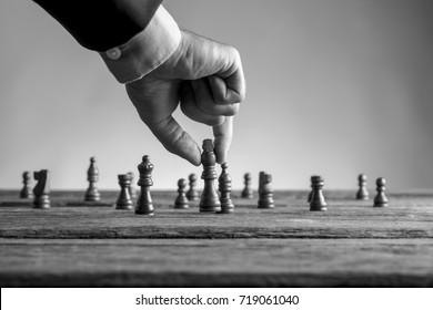Man in business suit playing chess moving the king piece lifting it up in his fingers in black and white. Conceptual of strategy planning.