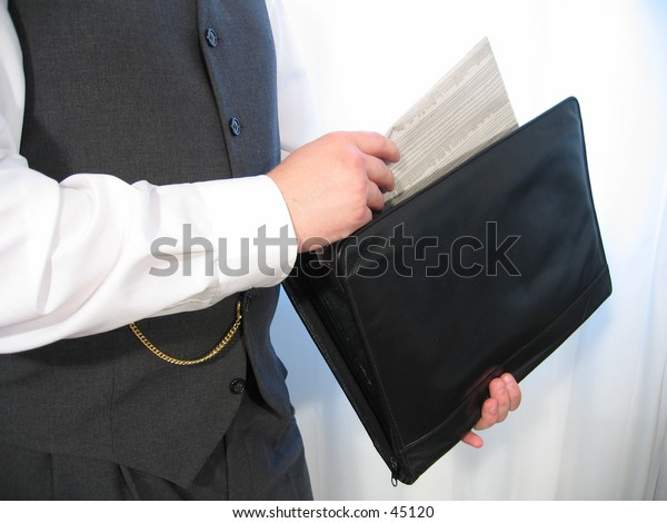 A man in a business suit pulls a newspaper out of his black briefcase.