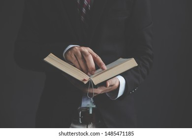 A man is business suit reading the Bible