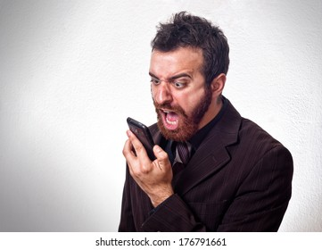 Man in business suit shouting into his mobile phone. Business concept
