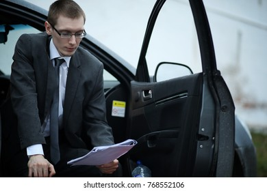 the man in a business suit is sitting in the car