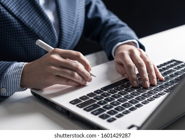 Man in business suit sitting at desk and working at laptop computer. Close-up of human hands holding pen and typing keyboard. Businessman at workplace in office. Business and digital technology
