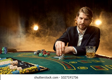 A man in a business suit sitting at the game table. Male player. Passion, cards, chips, alcohol, dice, gambling, casino - it is as male entertainment.
