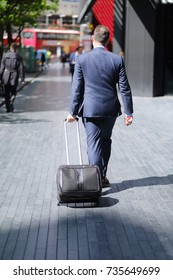 A man in a business suit with a suitcase walks along the sidewalk of London street