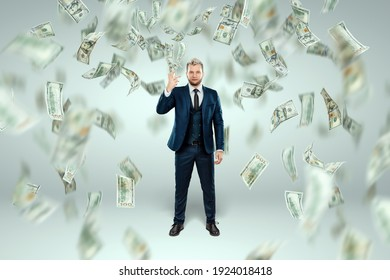 A man in a business suit tosses dollars up, it rains money. Business concept, bookmaker, sports betting, investment, passive income