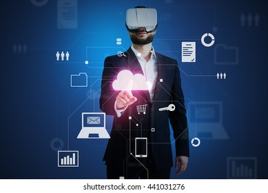 Man in business suit and VR-headset over dark blue background is touching a cloud icon on virtual interactive screen