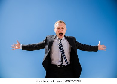 A man in a business suit waving his arms and shouting at the frame