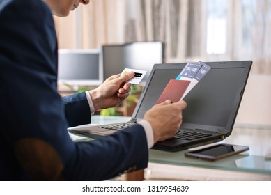 Man businessman holding airline ticket and debit card buying on the Internet using a laptop. The concept of purchasing and booking airline tickets online