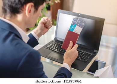 Man businessman holding airline ticket and passport buying on the Internet using a laptop. Purchasing and booking airline tickets online