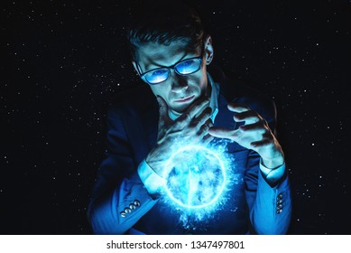 A man businessman holding hands over a blue glowing plasma sphere. Magic prediction and foresight in business and Finance