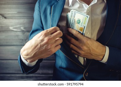 Man businessman, member or officer in a suit puts a bribe in the form of hundred dollar bills in his pocket. the concept of corruption and bribery among high-ranking officials