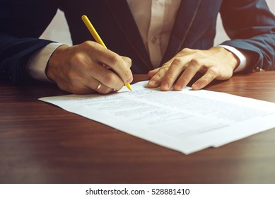 Man businessman signs documents with a pen making the signature sitting at the desk in the light. With retro effect.