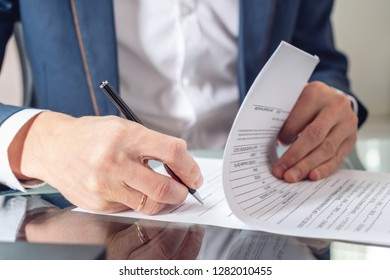 Man businessman sitting at the table signing documents in the office close up. Concept of registration of transactions and work with securities