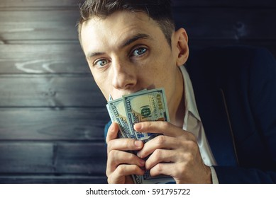 man businessman in a suit with a closed one hundred dollar bills mouth, silent for money. the concept of corruption and bribery