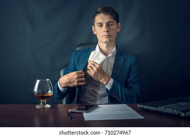 Man Businessman in suit puts money in his pocket. A bribe in the form of dollar bills. The concept of corruption and bribery