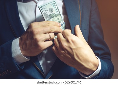man businessman in suit taking notes, bills of dollars in his pocket as a bribe. the concept of corruption and bribery