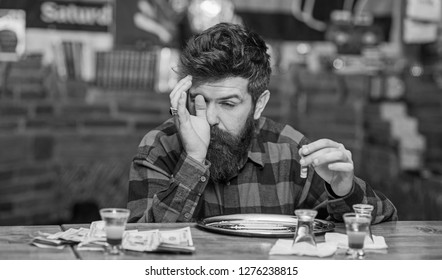 Man with busy face alone at bar counter, sniffing drug. Get high and dope concept. Hipster with beard sniffs cocaine, drug. Guy holds rolled banknote, defocused background.