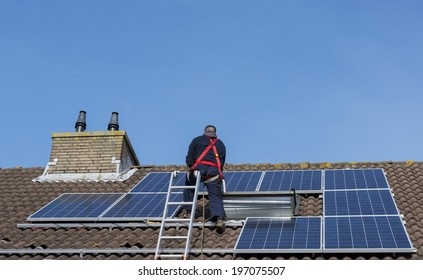 man is busy with solar panels construction on the roof near the cimney of roof of home