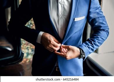 A man buttoning a blue jacket