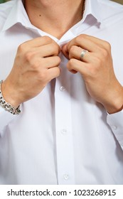 A man buttoning a button on a white shirt