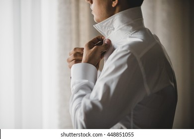 Man buttons up his white shirt standing in the front of a bright window