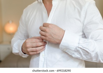 Man buttons sleeves on white linen dress shirt in bedroom at slight angle