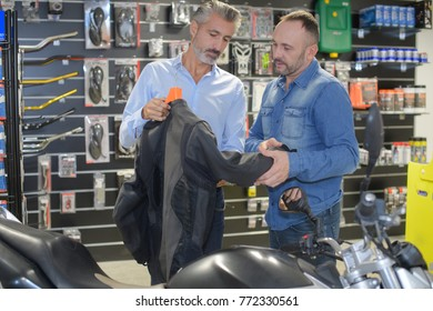 man buying a black leather jacket in a motorbike shop