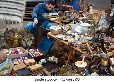 A man buying different antiques on flea market - aged vintage silver cultery - spoons, knifes, forks, and other vintage things. Collectibles memorabilia and garage sale concept. Selective focus