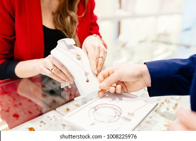 Man buying gift in jewelry store. Sale and customer service in the store